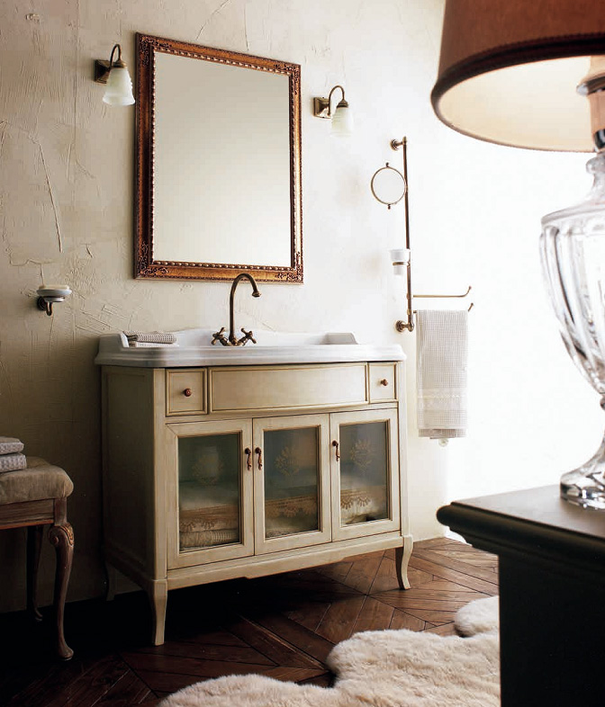 Victoria HPL105VPAT Белый с патиной/бронзаМебель для ванной<br>Напольная база под раковину Labor Legno Victoria с патинированием, прямоугольной формы с гнутыми ножками. На фасадной части – три распашных дверцы со стеклами и два небольших выдвижных ящика.<br>