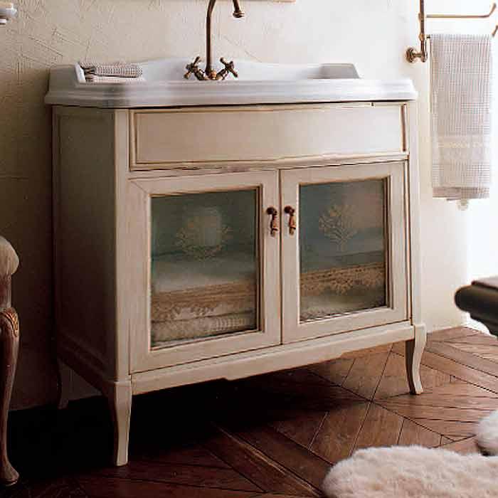 Victoria 90 Белый с патиной/БронзаМебель для ванной<br>Тумба на ножках Legno Victoria с двумя инкрустированными дверками со стеклом и раковиной прямоугольной формы 900x560 мм. Рабочая фурнитура и все ручки этой мебели изготовлены из бронзы.<br>